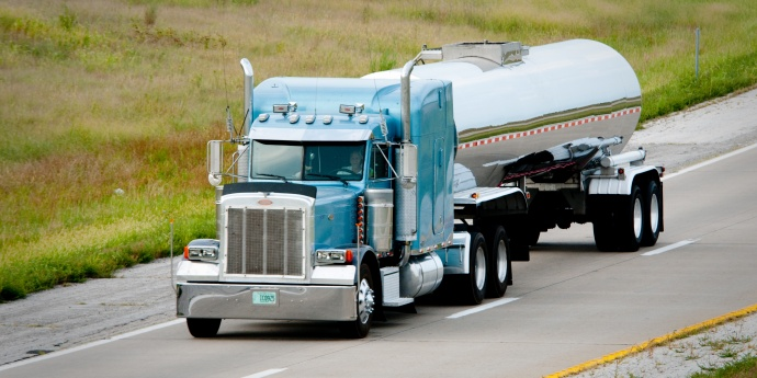 A large tanker truck with blue cab travels on highway
