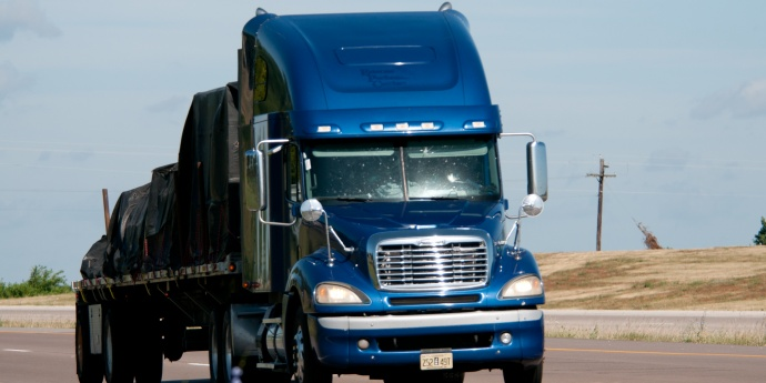 A dark blue semi truck pulls a covered load on a flatbed trailer
