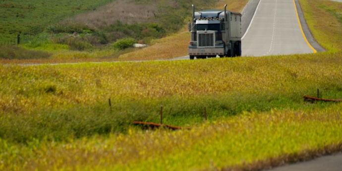 Dark semi truck drives down rural highway green median in foreground