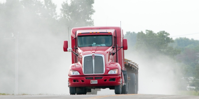 Red semi with flatbed trailer driving with dust rising up behind