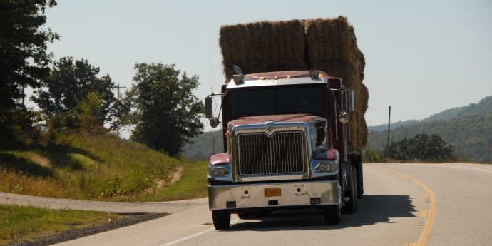 A front view of a red semi hauling bales of hay