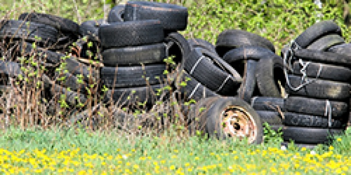 Image of used tires stacked in a field