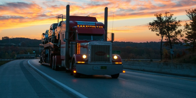 a semi truck drives under a sunset
