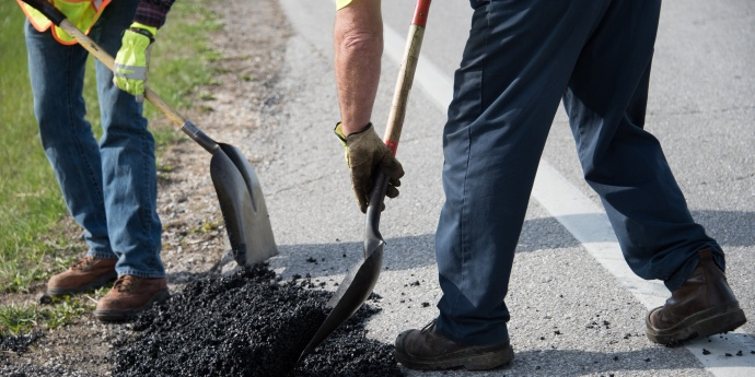 employees patch a pothole