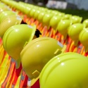 Rows of hardhats lined up on delineaters with safety vests