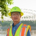 Engineer in PPE with bridge in background