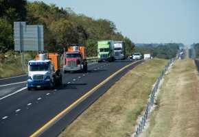 A line of four semis drive down a Missouri interstate
