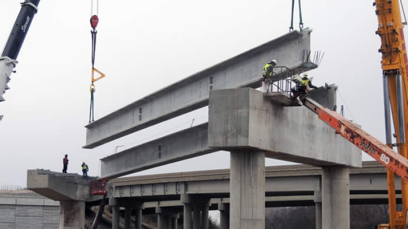 Crews lift one of the girders of the flyover ramp from 141 to I-44 into place