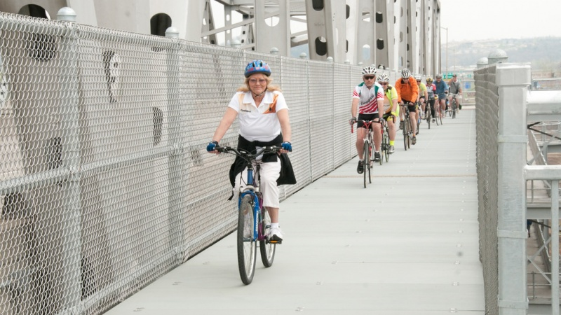 Person riding bicycle on bridge bike path