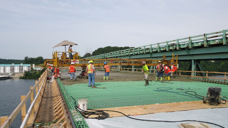 Construction crew pouring concrete on bridge deck