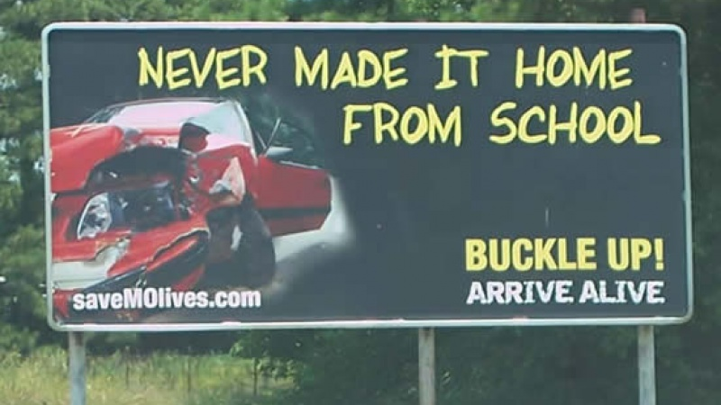 "Billboard stating ""Never made it home from school, buckle up, arrive alive."""