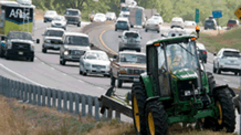 Tractor mowing alongside busy roadway