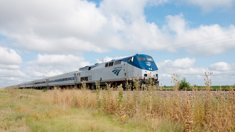 an amtrak train drives through a field