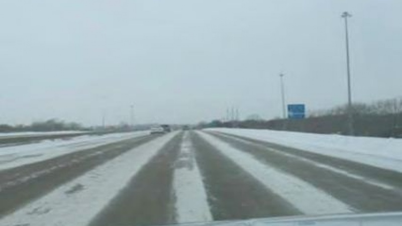 a highway partly covered in snow