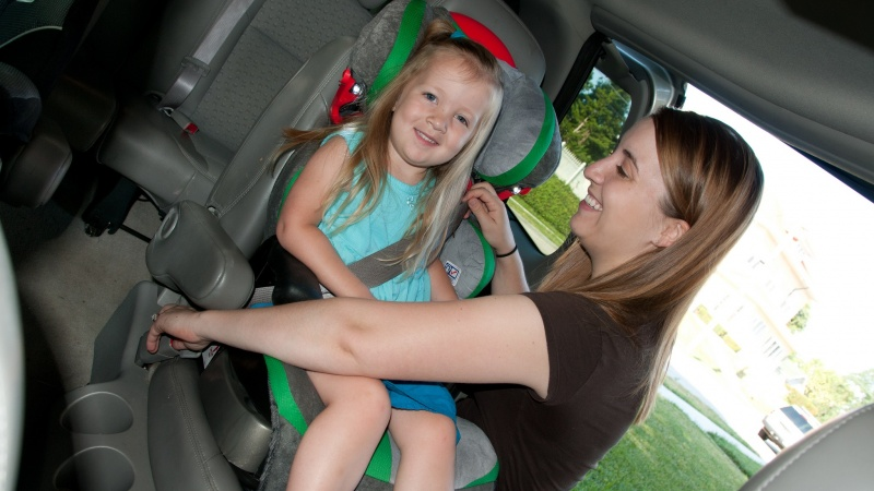 a woman secures a girl's booster seat