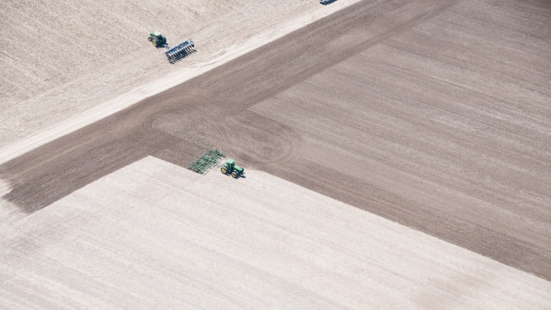 a bird's eye view of tractors working on a farm