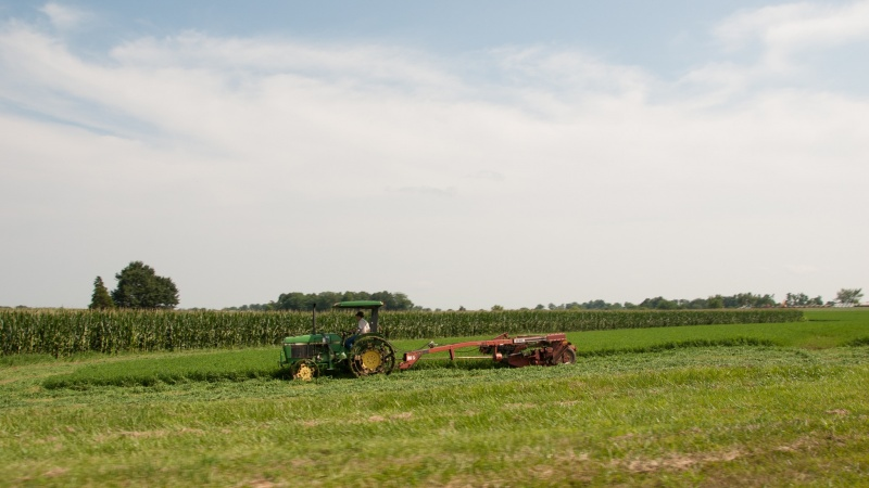 A tractor pulls equipment across a farm